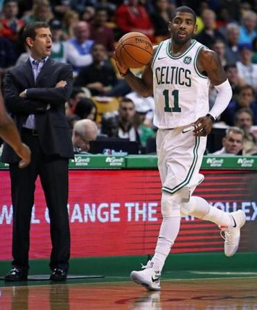 Boston, MA: October 2, 2017: The Celtics Kyrie Irving (right) dribbles by head coach Brad Stevens (left) during first quarter action. The Boston Celtics hosted the Charlotte Hornets in a pre season NBA basketball game at the TD Garden. (Jim Davis/Globe Staff).